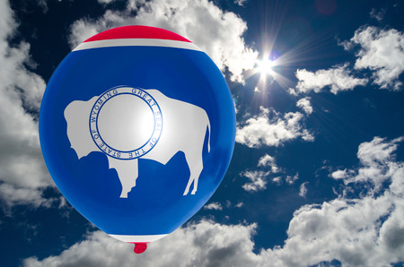 nationalistic: balloon in colors of wyoming flag flying on blue sky Stock Photo