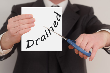 drained: Drained, man in suit cutting text on paper with scissors Stock Photo