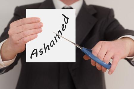 ashamed: Avergonzado, el hombre en traje de corte de texto en papel con tijeras