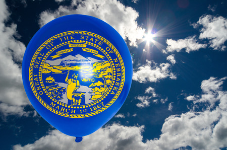 nationalistic: balloon in colors of nebraska flag flying on blue sky Stock Photo