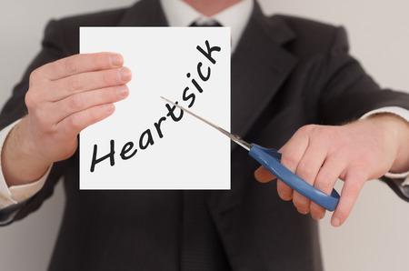 heartsick: Heartsick, hombre de traje de corte de texto en papel con tijeras Foto de archivo