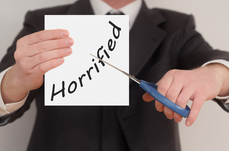 horrified: Horrified, man in suit cutting text on paper with scissors Stock Photo