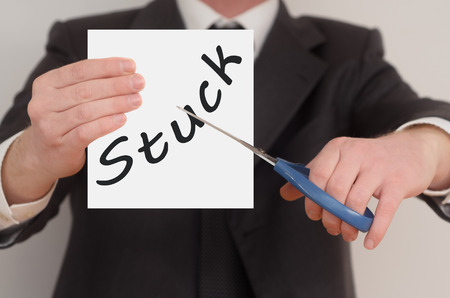 Stuck, man in suit cutting text on paper with scissors Stock Photo