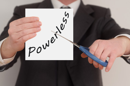 powerless: Powerless, man in suit cutting text on paper with scissors