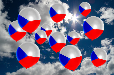 nationalistic: many ballons in colors of czech flag flying on sky