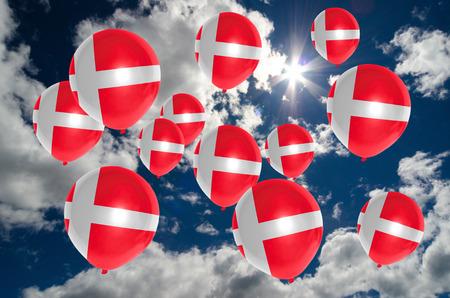 denmark flag: many ballons in colors of denmark flag flying on sky