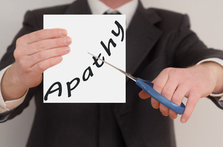 apathy: Apathy, man in suit cutting text on paper with scissors Stock Photo