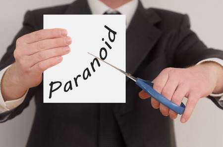 paranoid: Paranoid, man in suit cutting text on paper with scissors