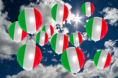 italian politics: many ballons in colors of italy flag flying on sky