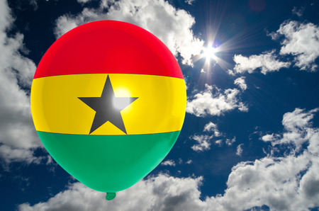 nationalistic: balloon in colors of ghana flag flying on blue sky