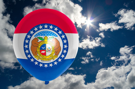 nationalistic: balloon in colors of missouri flag flying on blue sky