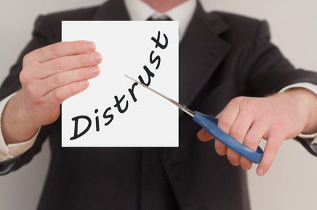 distrust: Distrust, man in suit cutting text on paper with scissors Stock Photo
