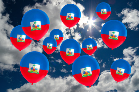 nationalistic: many ballons in colors of haiti flag flying on sky