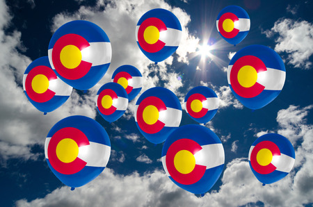 colorado flag: many ballons in colors of colorado flag flying on sky