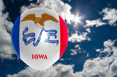 balloon in colors of iowa flag flying on blue sky photo