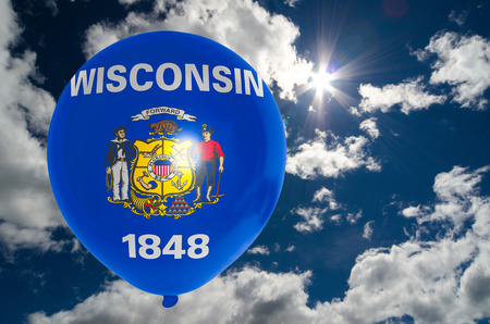 wisconsin flag: balloon in colors of wisconsin flag flying on blue sky