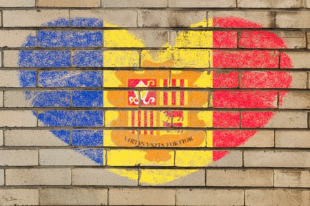 tourism in andorra: heart shaped flag in colors of andorra on brick wall