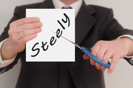 steely: Steely, man in suit cutting text on paper with scissors Stock Photo