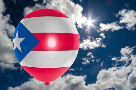 balloon in colors of puertorico flag flying on blue sky