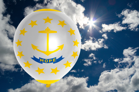nationalistic: balloon in colors of rhode island flag flying on blue sky Stock Photo