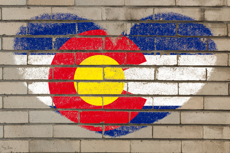 colorado flag: heart shaped flag in colors of colorado on brick wall Stock Photo