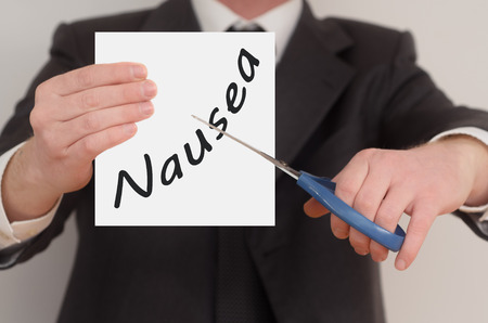Nausea, man in suit cutting text on paper with scissors