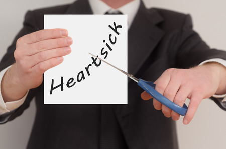 heartsick: Heartsick, man in suit cutting text on paper with scissors