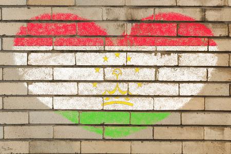 tajikistan: heart shaped flag in colors of tajikistan on brick wall