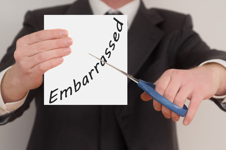 embarrassed: Embarrassed, man in suit cutting text on paper with scissors Stock Photo