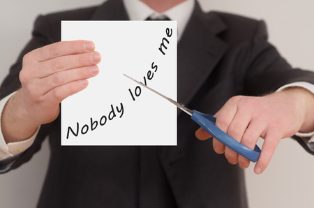 loves: Nobody loves me, man in suit cutting text on paper with scissors