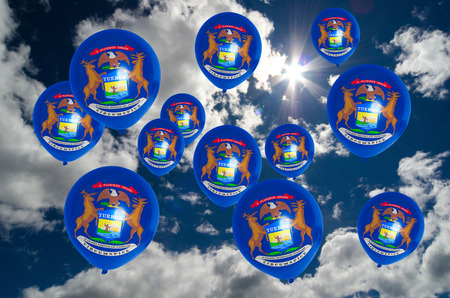michigan flag: many balloons in colors of michigan flag flying on sky