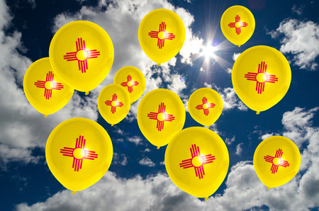 many balloons in colors of new mexico flag flying on sky Stock Photo
