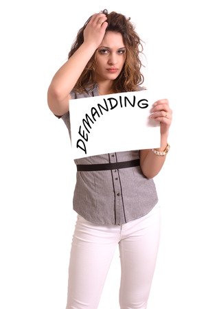 demanding: Young attractive woman holding paper with Demanding text on white background Stock Photo