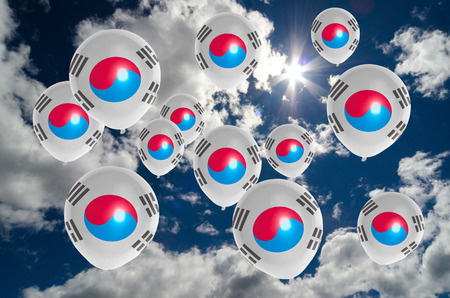 many balloons in colors of south korea flag flying on sky