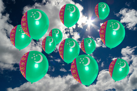 many balloons in colors of turkmenistan flag flying on sky