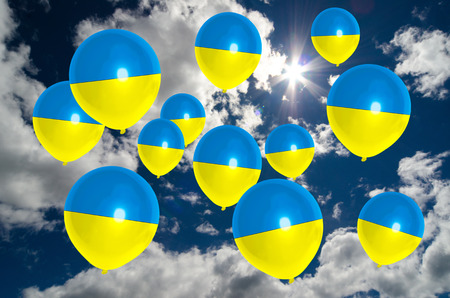 many balloons in colors of ukraine flag flying on sky