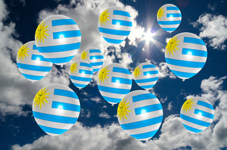 many balloons in colors of uruguay flag flying on sky