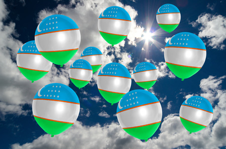 many balloons in colors of uzbekistan flag flying on sky