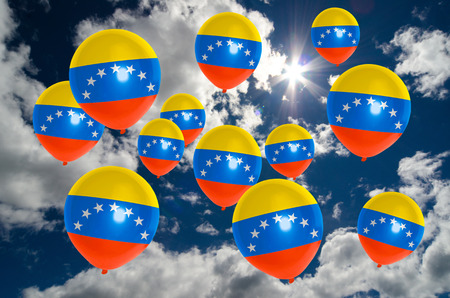 many balloons in colors of venezuela flag flying on sky Stock Photo