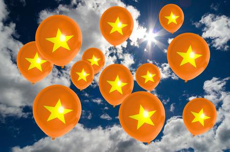 vietnam flag: many balloons in colors of vietnam flag flying on sky Stock Photo