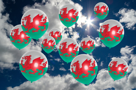 many balloons in colors of wales flag flying on sky