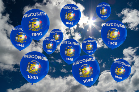 wisconsin flag: many balloons in colors of wisconsin flag flying on sky Stock Photo