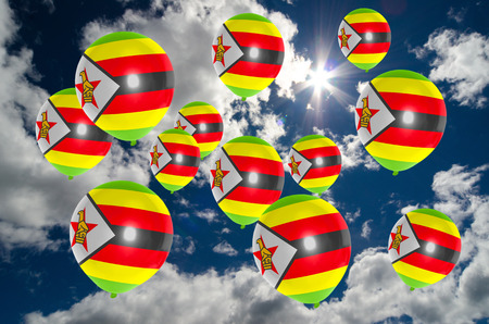 many balloons in colors of zimbabwe flag flying on sky
