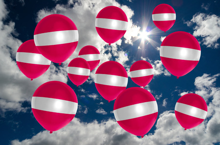many balloons in colors of latvia flag flying on sky Stock Photo