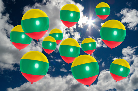 many balloons in colors of lithuania flag flying on sky