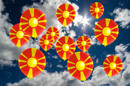 many balloons in colors of macedonia flag flying on sky