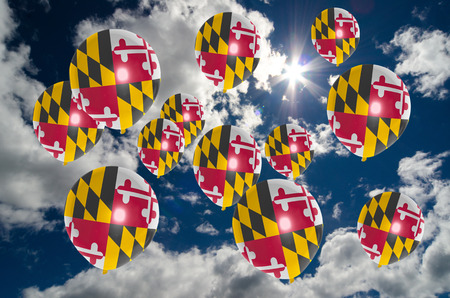many balloons in colors of maryland flag flying on sky