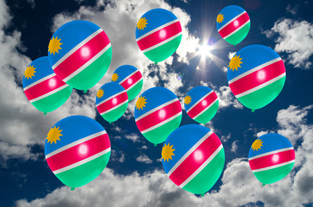 many balloons in colors of namibia flag flying on sky