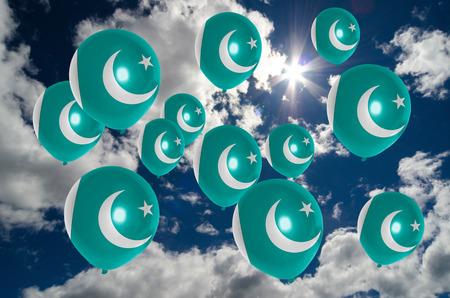 pakistan flag: many balloons in colors of pakistan flag flying on sky