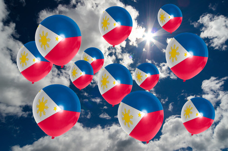 many balloons in colors of philippines flag flying on sky